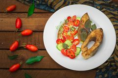 Grilled fish steak with vegetables on plate: tomatoes, microgran, cucumber, tasty and healthy dinner. Wooden rustic background. To. P view Royalty Free Stock Photography