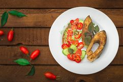Grilled fish steak with vegetables on plate: tomatoes, microgran, cucumber, tasty and healthy dinner. Wooden rustic background. To. P view Royalty Free Stock Image