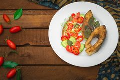 Grilled fish steak with vegetables on plate: tomatoes, microgran, cucumber, tasty and healthy dinner. Wooden rustic background. To. P view Royalty Free Stock Photos