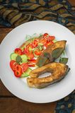 Grilled fish steak with vegetables on plate: tomatoes, microgran, cucumber, tasty and healthy dinner. Wooden rustic background. To. P view Stock Photos