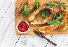 Grilled fish tilapia and chili plantains with arugula Stock Images