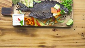 Grilled fish with vegetable garnish in barbecue restaurant. Food composition fish bbq with vegetable on wooden table. Appetizing dishes in seafood restaurant stock video footage