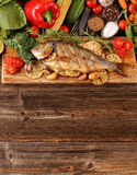 Grilled fish with vegetables on old wooden background with space Royalty Free Stock Photos