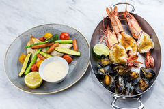 Grilled fish and vegetables with sauce with royal prowns and mussle Stock Images