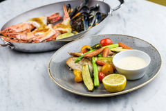 Grilled fish and vegetables with sauce with royal prowns and mussle Stock Photos