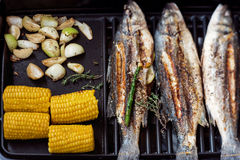 Grilled Fish with vegetables. Grilled tasty fresh fish with onion, corn and asparagus Royalty Free Stock Image