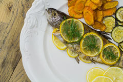 Grilled fish with vegetables on wooden table Royalty Free Stock Photography