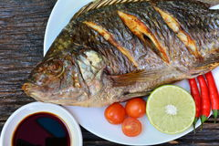 Grilled fish on white plate with chili pepper, lemon and tomato stock images