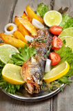 Grilled fish on wooden table Stock Photo