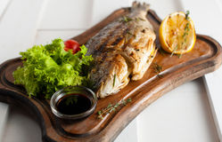 Grilled fish & x28;Dorado& x29; on a wooden board with lemon, salad, sauce and cherry tomatoes Stock Image