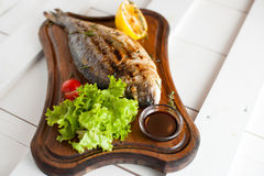 Grilled fish & x28;Dorado& x29; on a wooden board with lemon, salad, sauce and cherry tomatoes Stock Images