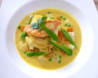 Grilled fish with yellow curry sauce isolated on white. stock photos