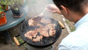 Man turn over large delicious meat steaks, which roast over the coals on barbecue. Grilled food. Meat steak. Man turn over large delicious meat steaks, which stock footage
