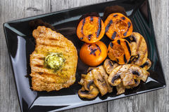 Grilled food. Pork steak with seasoned butter , mushrooms and nectarines on wooden surface , top view Royalty Free Stock Photos