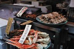 Grilled food on sale. Plates of grilled food on sale in Tsukiji Fish Market, Tokyo, Japan. Includes King Crab (Taraba-gani), Eel (Unagi) and eel innards (Unagi Royalty Free Stock Images