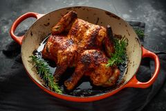 Grilled fried roast Chicken Tabaka in frying pan with rosemary.  stock photo