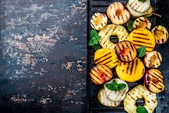 GRILLED FRUITS. Grill fruits - pineapple, peaches, plums, avocado, pear on black cast iron grill board. Copy space royalty free stock image