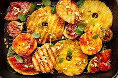 Grilled fruits; pineapples, peaches, figs, pears and watermelon with pine nuts, fresh herbs and honey on the grill plate, top view royalty free stock images