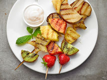 Grilled fruits on wooden skewers Stock Images