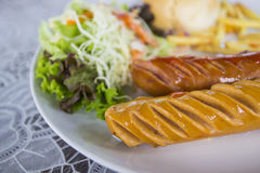 Grilled german sausage. With salad, bun and french fried Royalty Free Stock Image