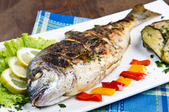 Grilled gilt head sea bream on plate with lemon ,salad and grill. Grilled gilt head sea bream on plate with lemon salad and grilled vegetables royalty free stock photography