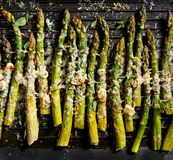 Grilled green asparagus with the addition of parmesan cheese, garlic and aromatic herbs on the grill plate,. Top view, close-up stock photography