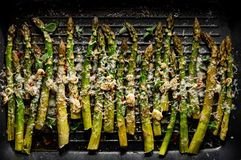 Grilled green asparagus with the addition of parmesan cheese, garlic and aromatic herbs on the grill plate,. Top view stock image