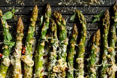 Grilled green asparagus with the addition of parmesan cheese, garlic and aromatic herbs on the grill plate,. Top view, close-up royalty free stock photography