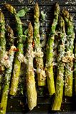 Grilled green asparagus with the addition of parmesan cheese, garlic and aromatic herbs on the grill plate,. Top view, close-up stock images