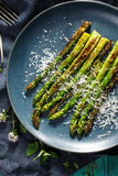 Grilled green asparagus with addition of parmesan cheese on a plate Royalty Free Stock Photo