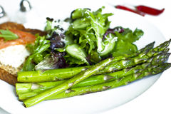Grilled green asparagus. Breakfast: Grilled green asparagus with salad-mix and toast with poached egg Stock Image