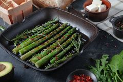 Grilled green asparagus in a frying pan with ingredients around. vegetables, gluten free bread, eggs and parsley. Flat lay. stock image