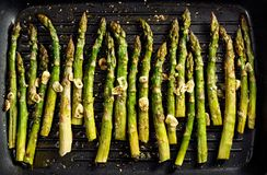 Grilled green asparagus with garlic, olive oil and aromatic spices on the grill plate, top view. Vegan food stock photos