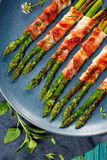 Grilled green asparagus wrapped with bacon on blue plate Royalty Free Stock Image