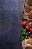 Grilled ground beef meat Burger steak cutlets with seasoning, tomatoes, parsley and bun on wooden table, space for text. Royalty Free Stock Images