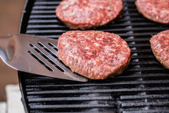 Grilled ground beef pattie burger on spatula Stock Images
