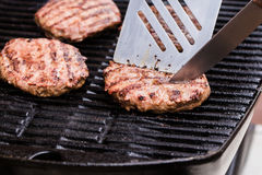 Grilled ground beef pattie burger with spatula and Royalty Free Stock Images