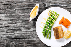 Grilled hake served with asparagus, piece of lemon, baby carrots Royalty Free Stock Photos