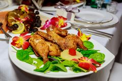 Grilled half chicken served on a plate, napkin and silverware, background fades to white,. Selected focus, narrow depth of field Royalty Free Stock Photography