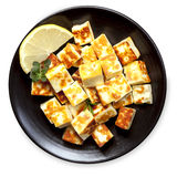 Grilled Halloumi Cheese with Lemon and Herbs. Grilled halloumi cheese cubes with lemon and herbs.  On black plate, top view, isolated on white Royalty Free Stock Images
