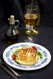 Grilled Halloumi Cheese. In a plate with a glass of wine and a olive oil bottle Stock Photography