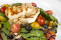 Grilled Halloumi Cheese poured with garlic olive oil salad witch grilled eggplant, cherry tomatoes, black olives and spinach royalty free stock photos