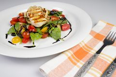 Grilled Halloumi Cheese poured with garlic olive oil salad witch grilled eggplant, cherry tomatoes, black olives and spinach stock photos