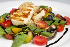 Grilled Halloumi Cheese poured with garlic olive oil salad witch grilled eggplant, cherry tomatoes, black olives and spinach stock image