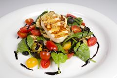 Grilled Halloumi Cheese poured with garlic olive oil salad witch grilled eggplant, cherry tomatoes, black olives and spinach stock photography