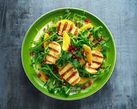 Grilled Halloumi Cheese salad with orange, rocket leaves, pomegranate and pumpkin seed. healthy food.  Royalty Free Stock Photography