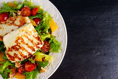 Grilled Halloumi Cheese salad witch orange, tomatoes and lettuce. healthy food Royalty Free Stock Images