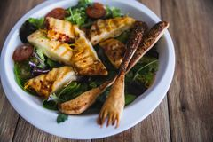 Grilled Halloumi Cheese salad witch tomatoes and lettuce in white plate in wooden background. healthy food royalty free stock photos