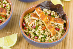 Grilled Halloumi and Tabbouleh. Salad made with bulghur wheat, tomato, parsley and pomegranate seeds topped with grilled halloumi Royalty Free Stock Image
