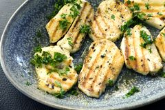 Grilled Haloumi Cheese in Bowl topped with parsley. Grilled haloumi cheese in stone serving dish, topped with parsley stock photography